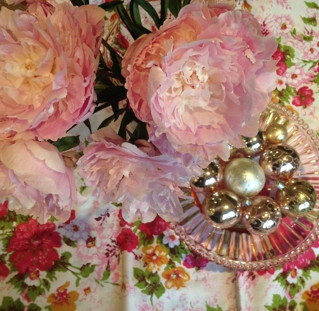 Peonies and baubles in pink cake stand with vintage sheet as tablecloth